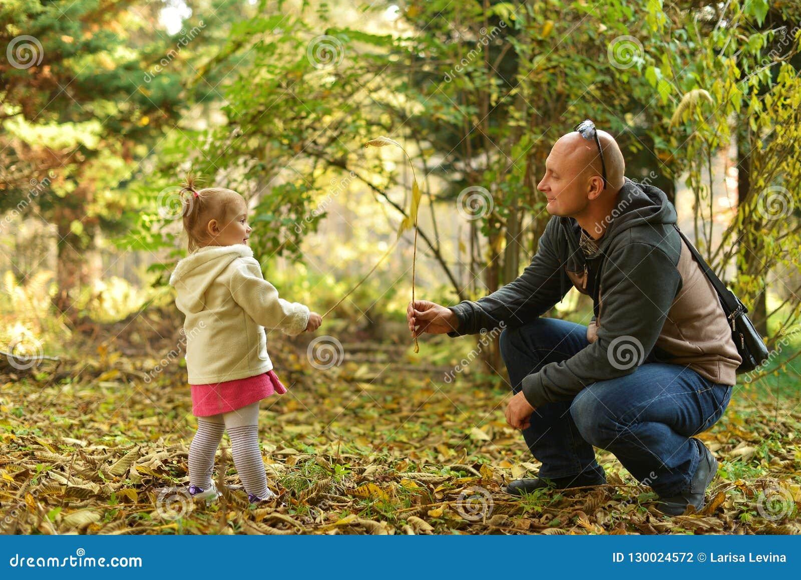 Menina com o paizinho que anda na floresta no outono