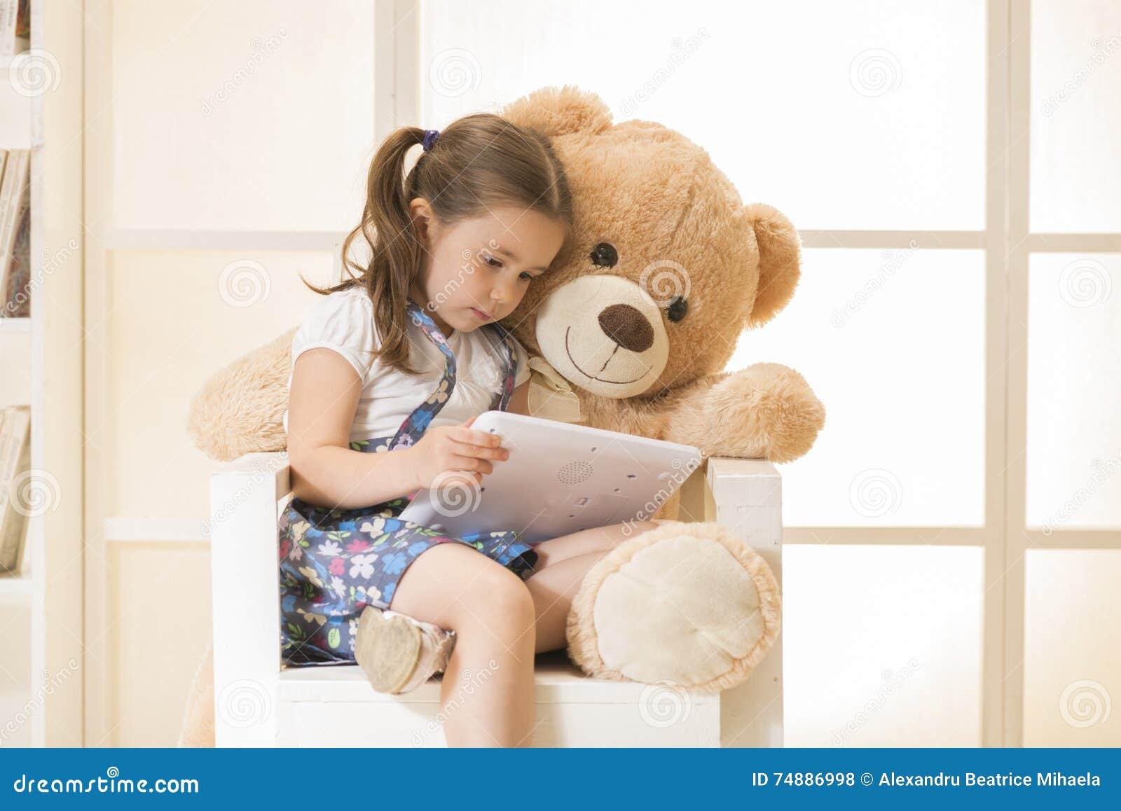 Menina com o urso de peluche que olha seu tablet pc