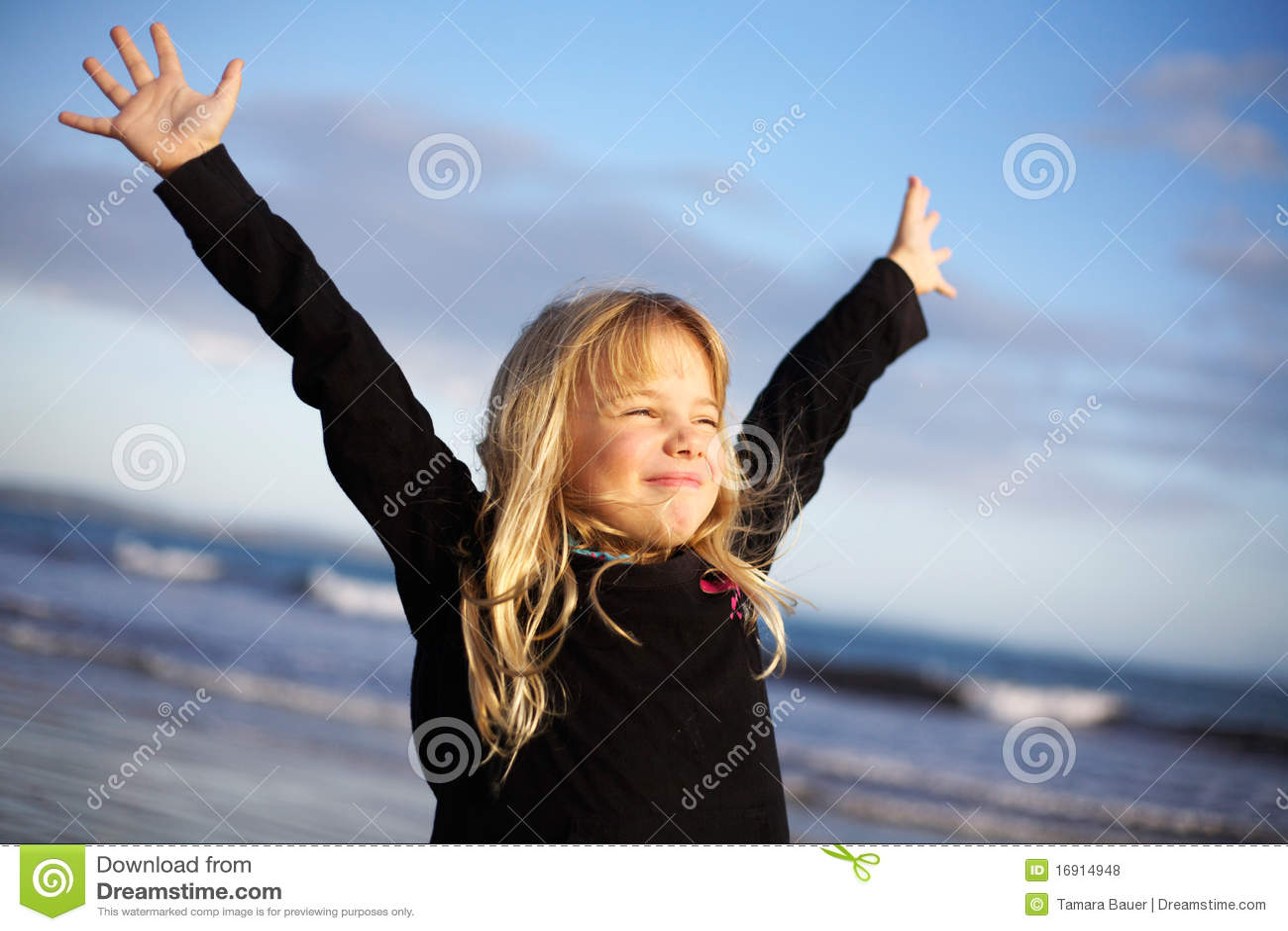 Menina com os braços outstretched na praia