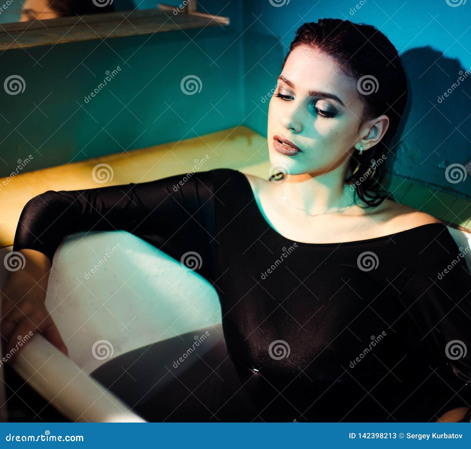 Menina com os ombros desencapados que encontram-se no banheiro com água roxa colorida Conceito da forma