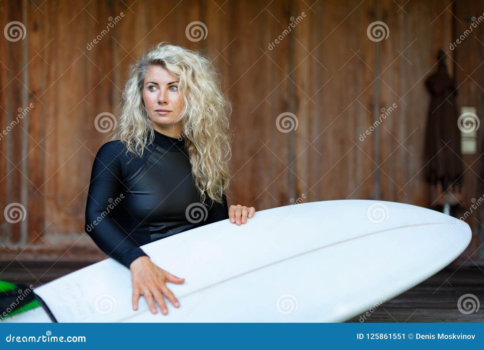 A menina com prancha senta-se em etapas da varanda da casa de campo da praia