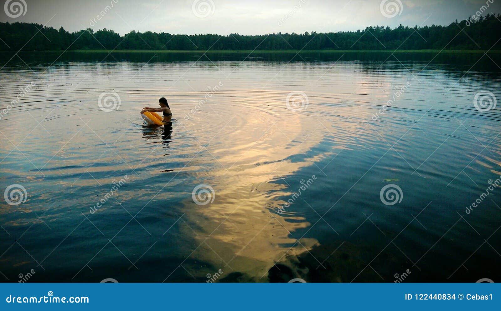 Menina com a roda de água no lago na noite
