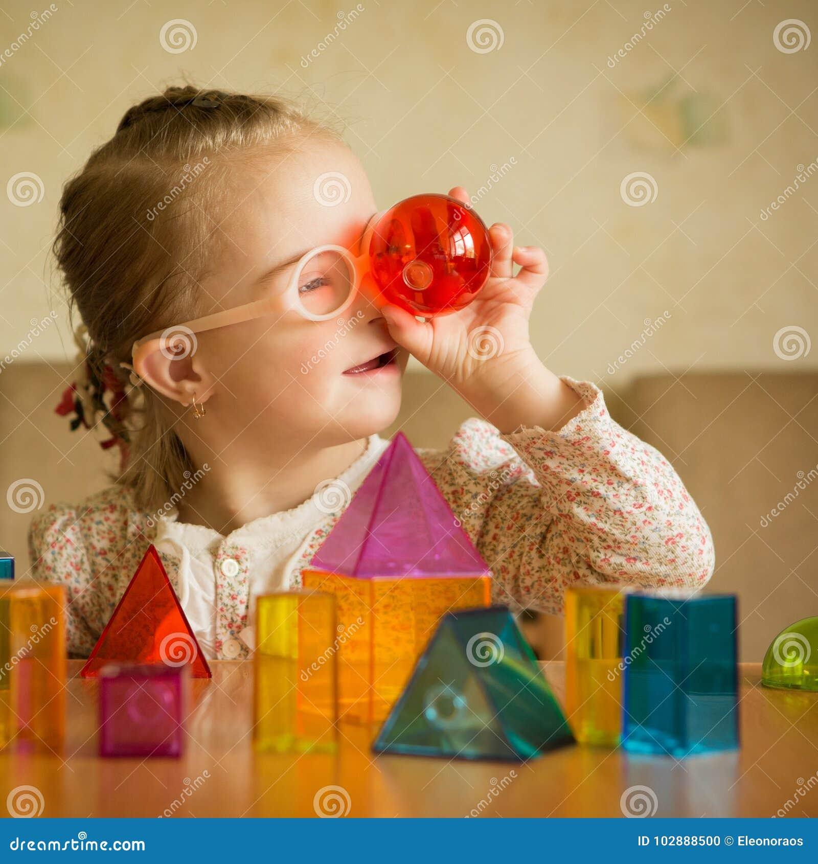 Menina com a Síndrome de Down que joga com formas geométricas