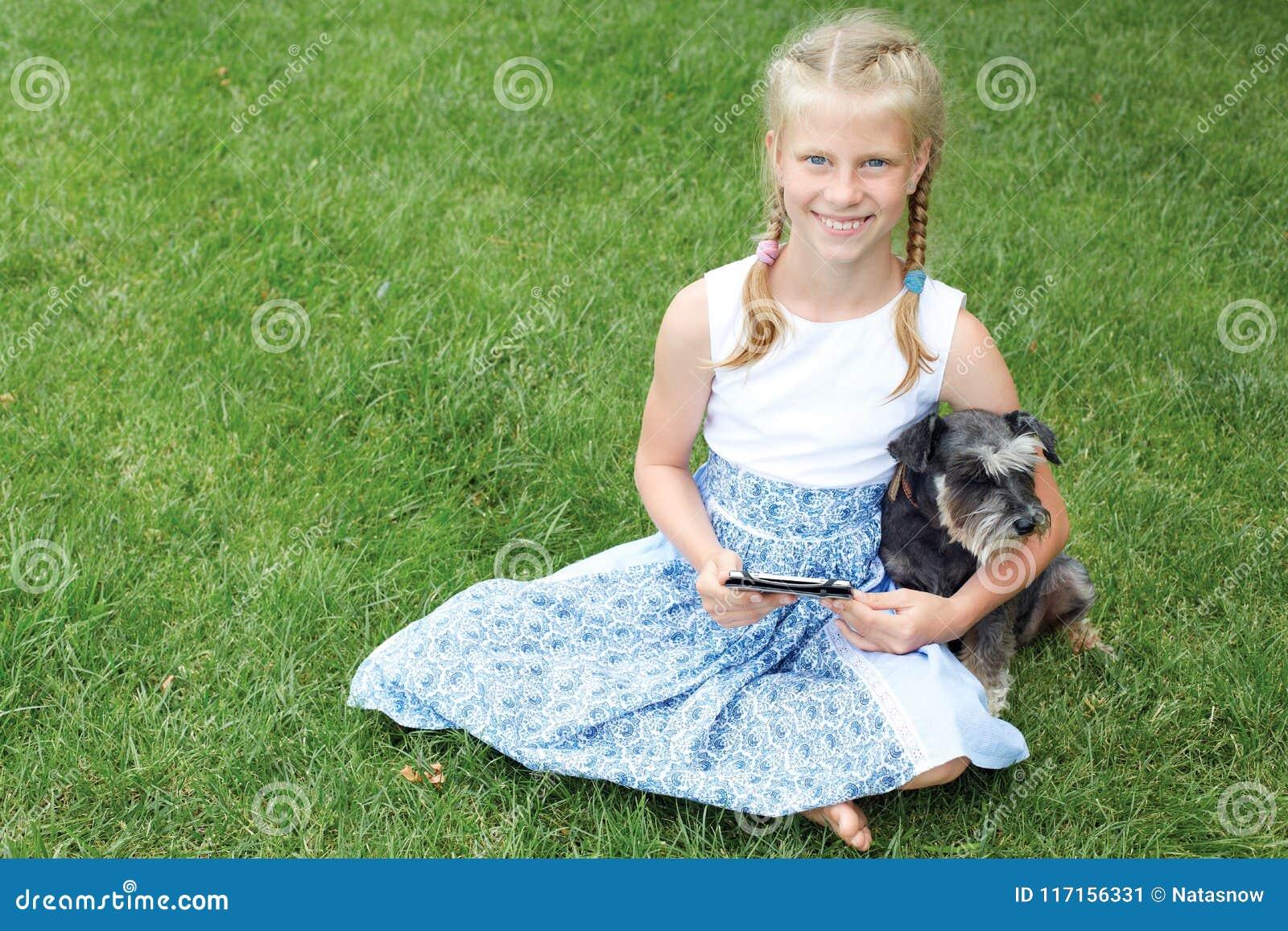 Menina com seu cão que senta-se na grama verde e no eBook lido