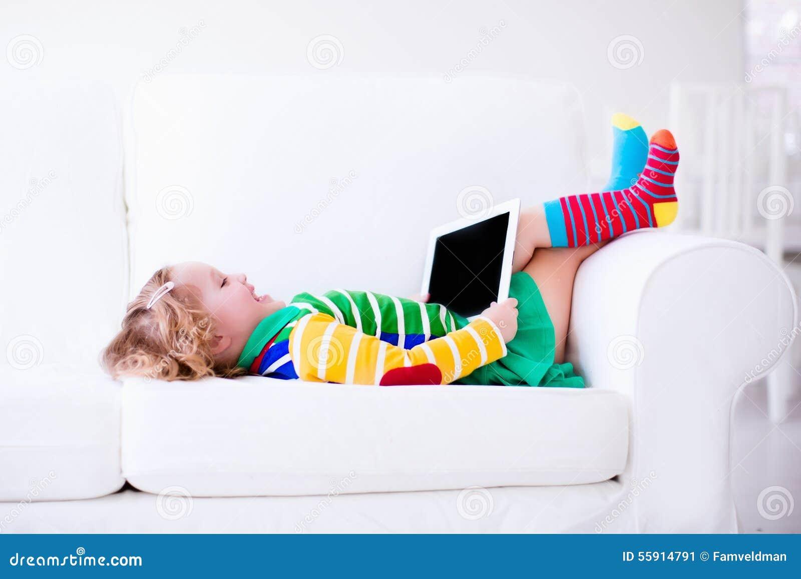 Menina com tablet pc em um sofá branco