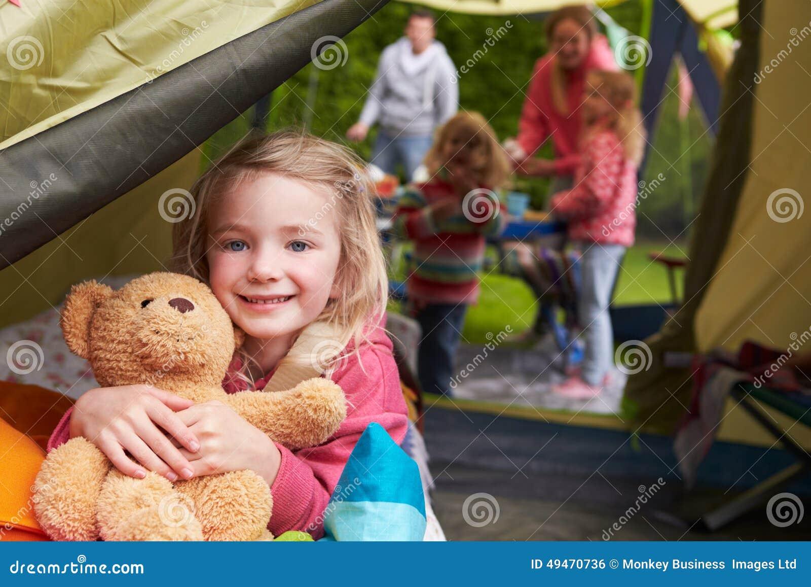 Menina com Teddy Bear Enjoying Camping Holiday no acampamento