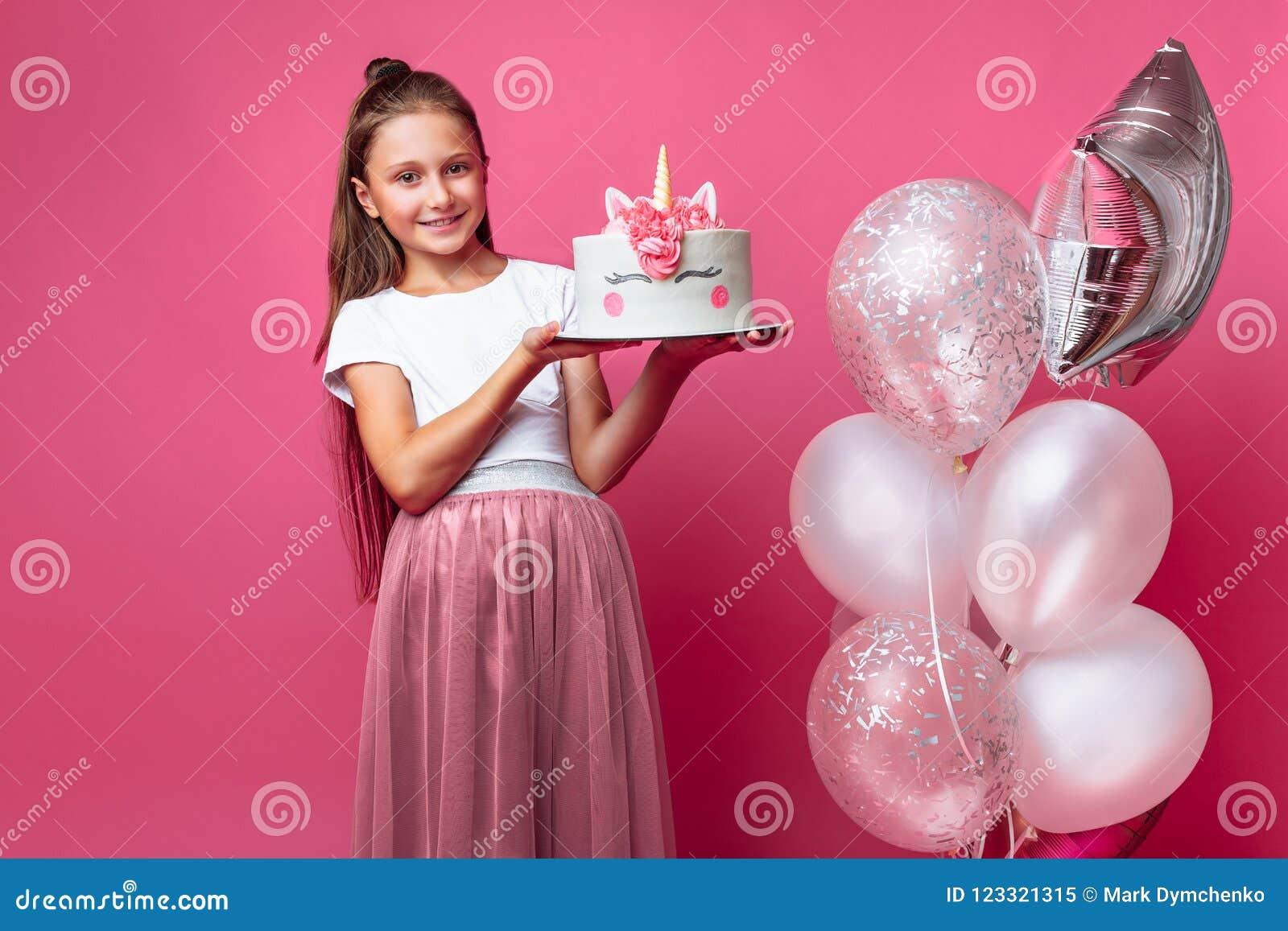 Menina com um bolo para um aniversário, no estúdio em um fundo cor-de-rosa, humor festivo