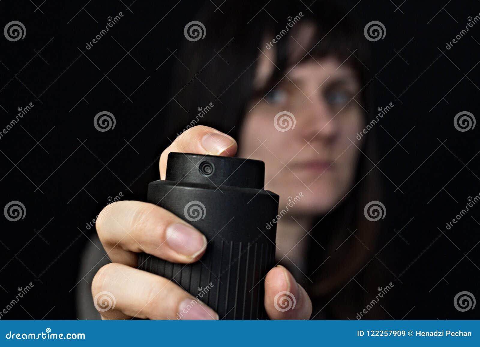 Menina com um g?s, spray de pimenta, close-up, fundo preto