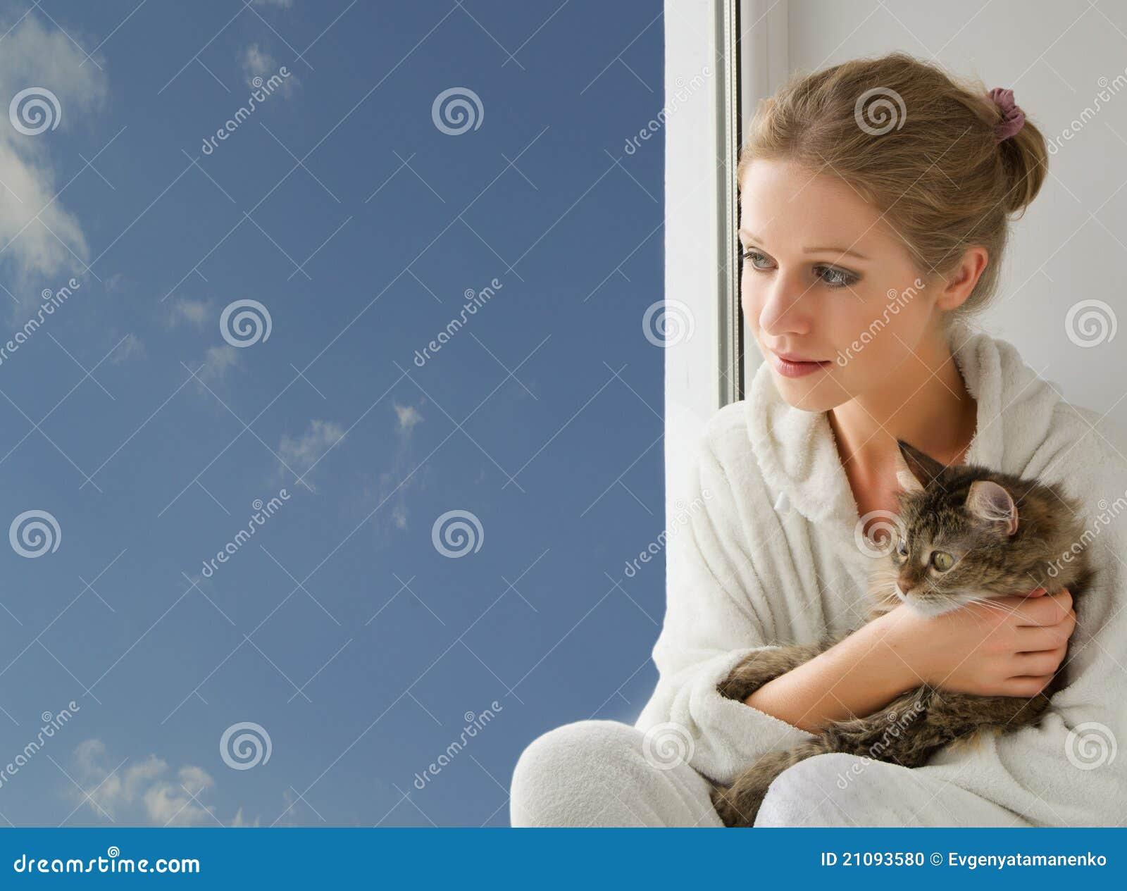 Menina com um gato que olha para fora o indicador