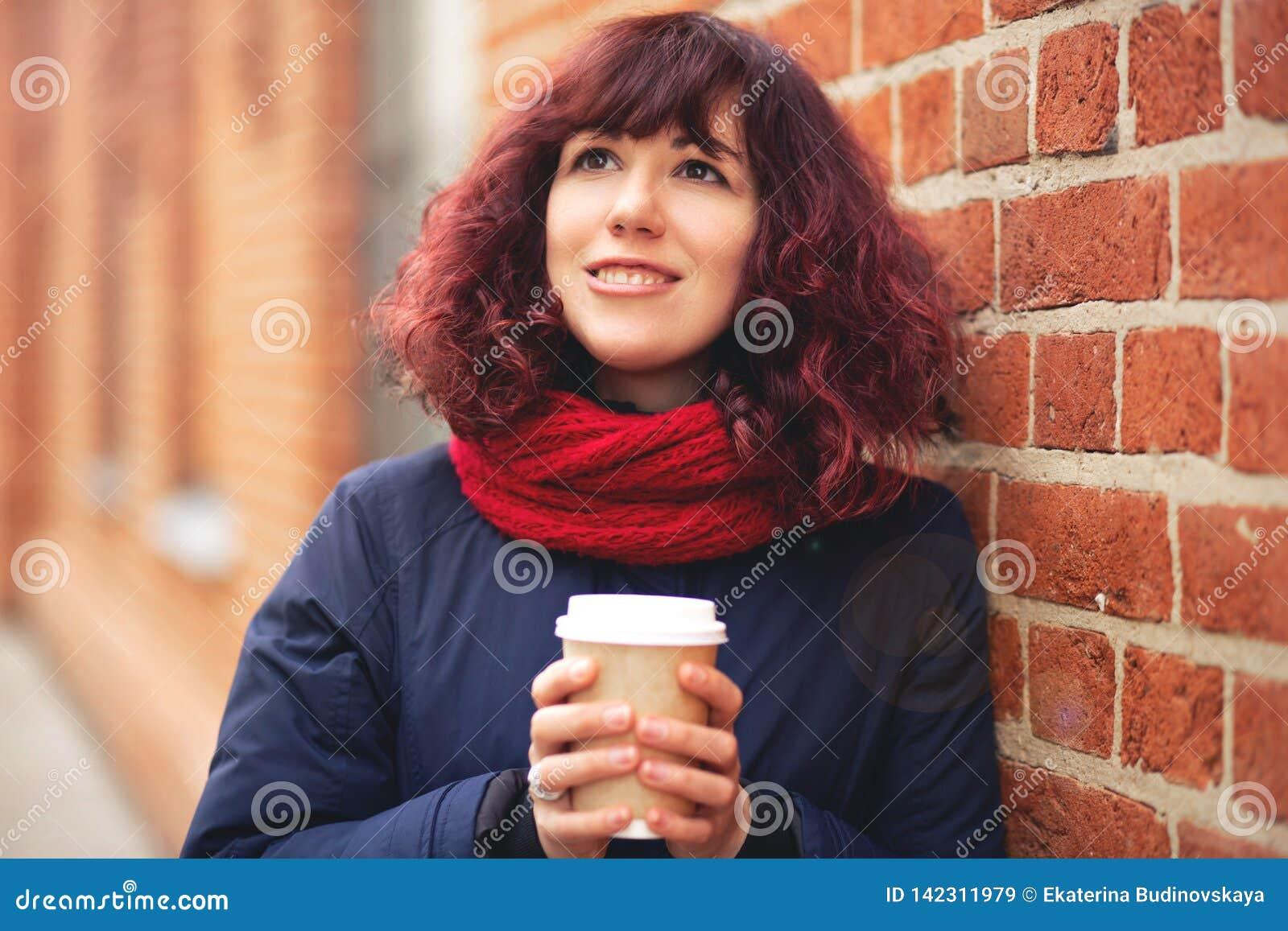 Menina com um vidro do café à disposição
