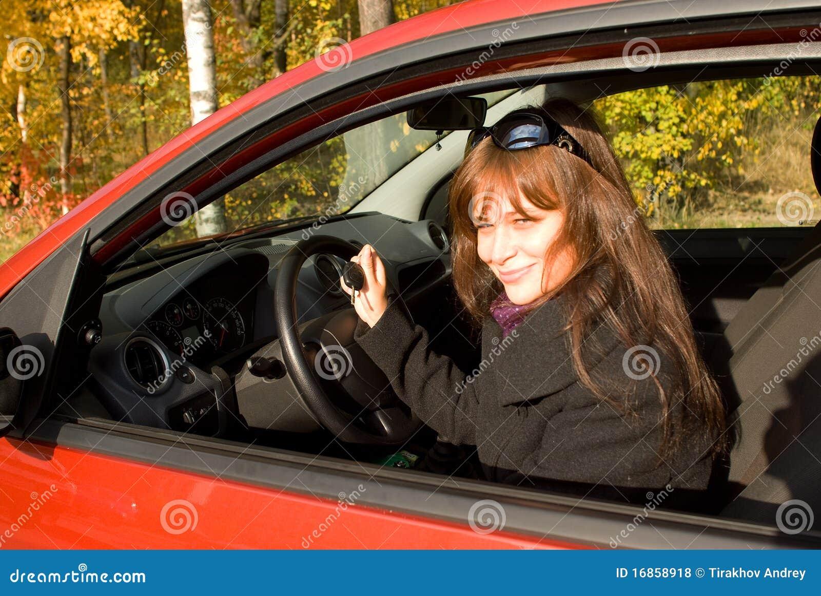 A menina com uma chave no carro vermelho