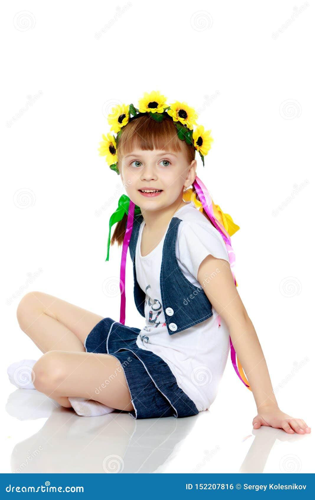 Menina com uma grinalda bonita das flores em sua cabe?a
