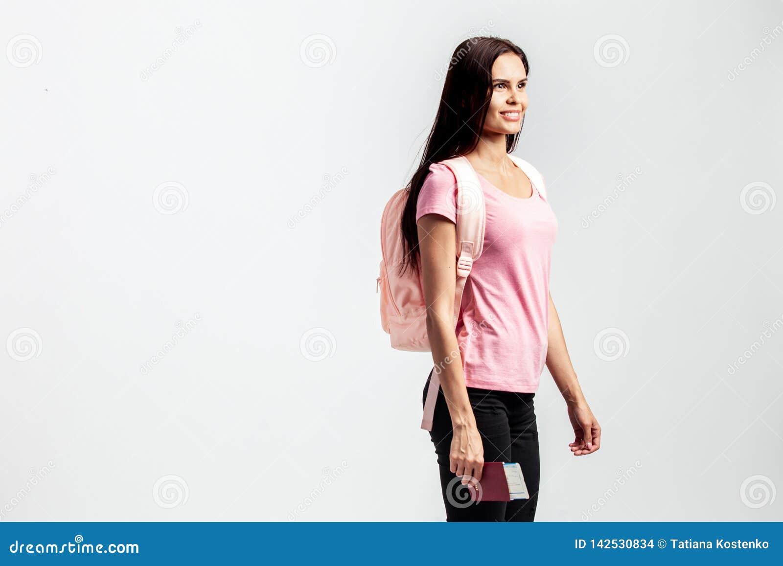 Menina com uma trouxa em seus ombros vestido no t-shirt cor-de-rosa