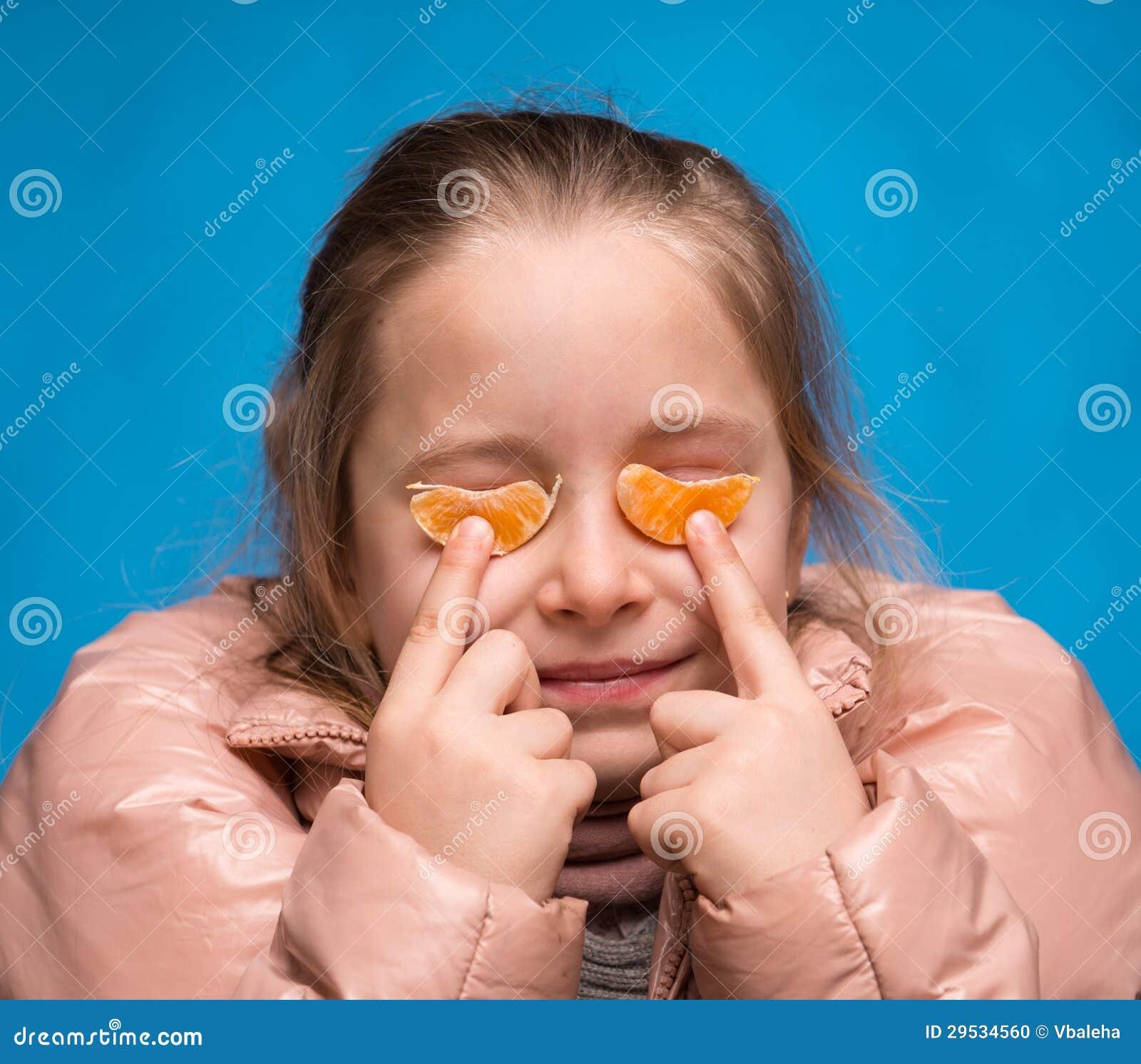 Menina com vidros da tangerina