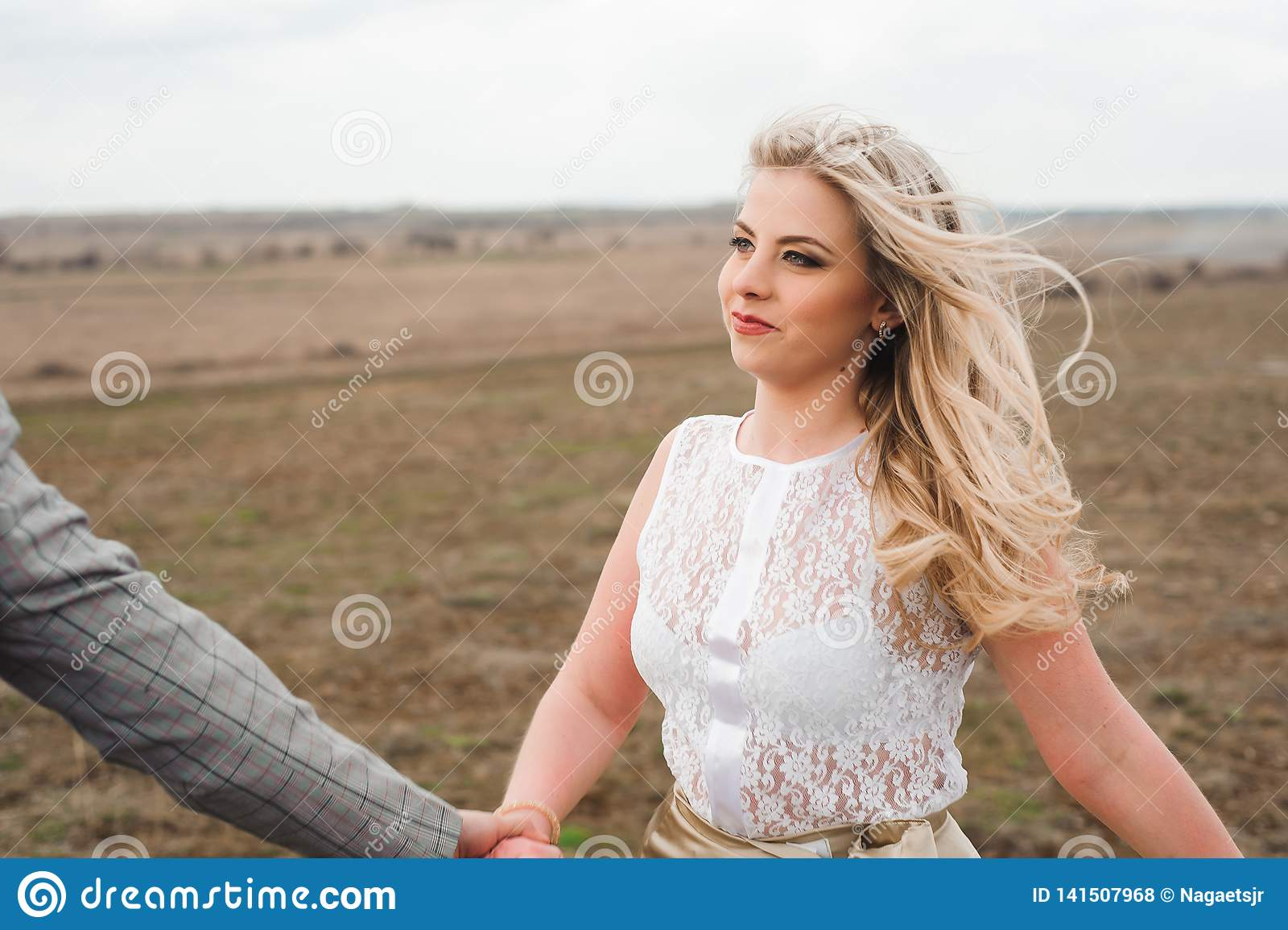A menina considerável do indivíduo e do louro que anda no campo, um homem conduz uma mulher que guarda a mão