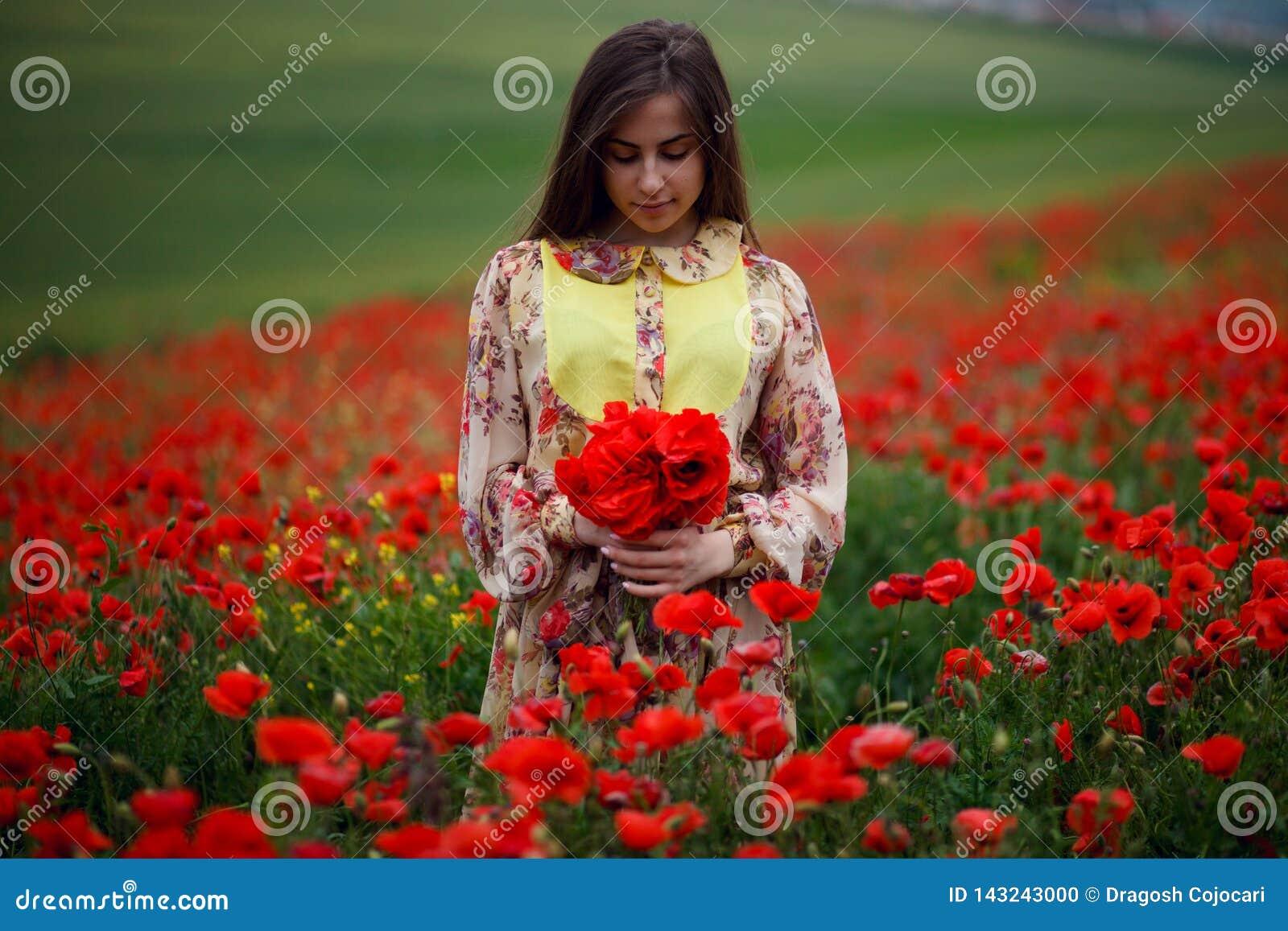 Menina considerável que veste no vestido floral do verão, assentado nas papoilas campo, terras arrendadas um ramalhete das flores
