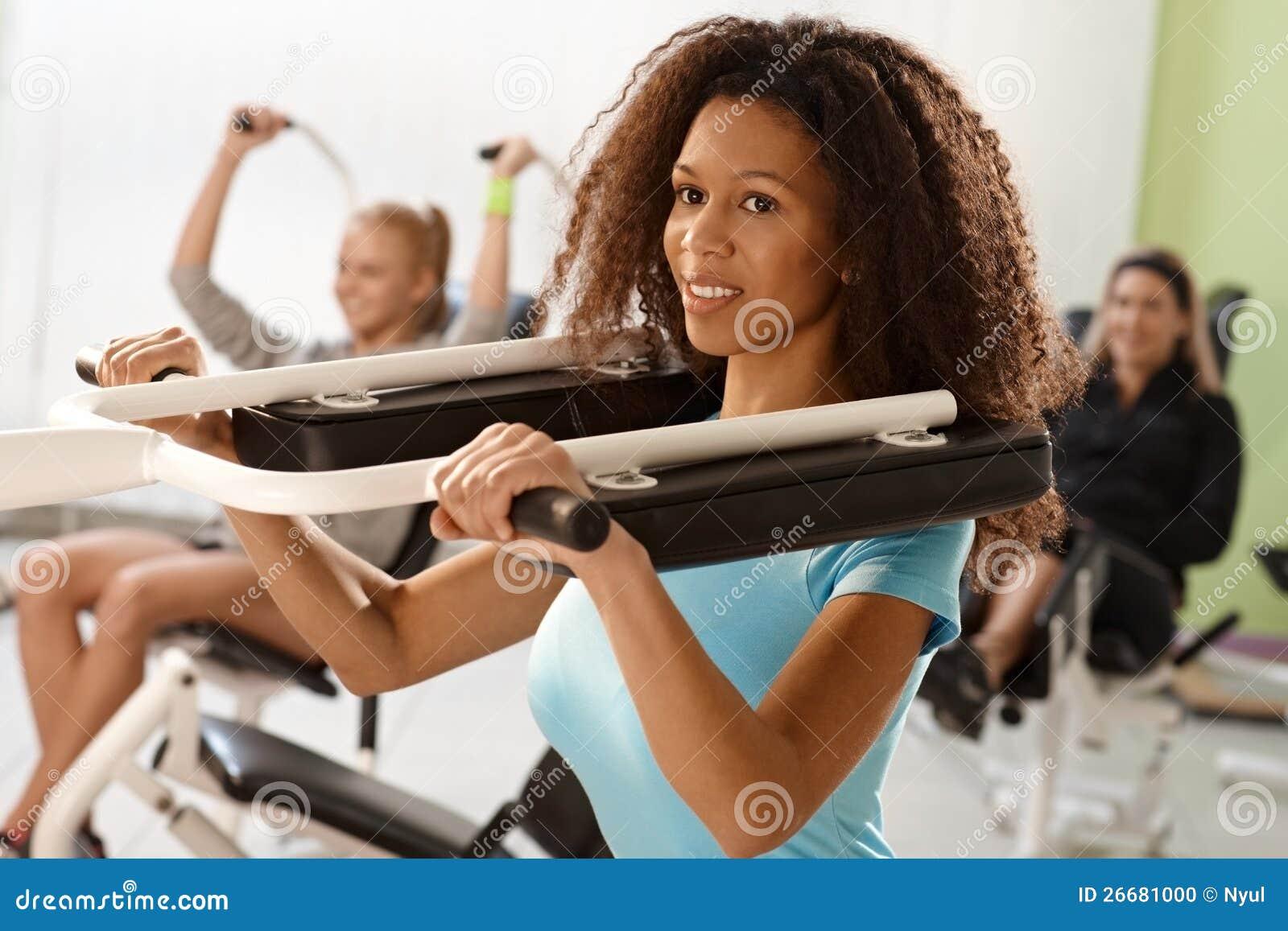 Menina consideravelmente étnica que exercita na máquina do peso