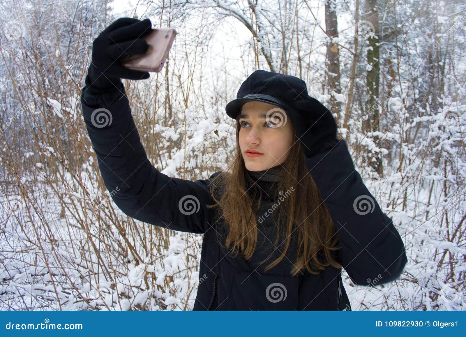 A menina consideravelmente adolescente da forma faz o retrato do selfie na floresta nevado do inverno