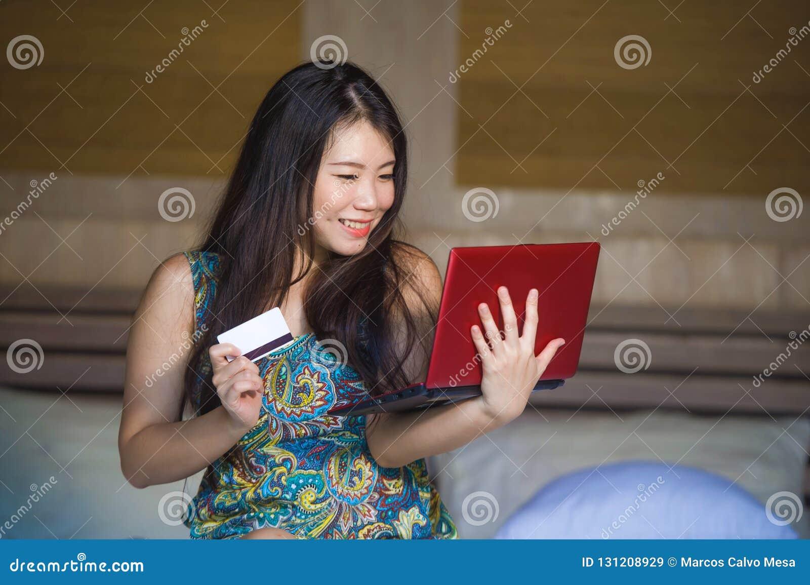Menina coreana asiática bonita e feliz nova que usa Internet banking do cartão de crédito no laptop em casa na cama s entusiasmad
