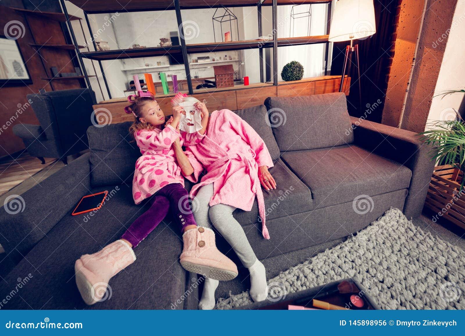 Menina curiosa que tem muito divertimento ao pôr a máscara da folha sobre a avó