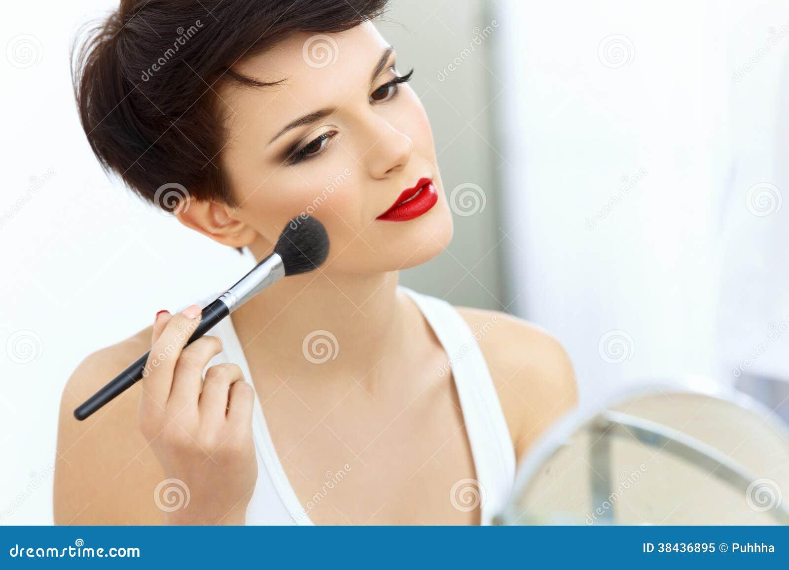 Menina da beleza com escova da composição. Natural compense pela mulher moreno com bordos vermelhos.