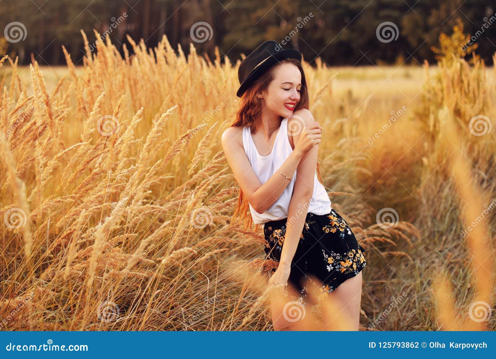 Menina da beleza que aprecia fora a natureza Modelo consideravelmente adolescente no chapéu que corre no campo da mola, luz de Su
