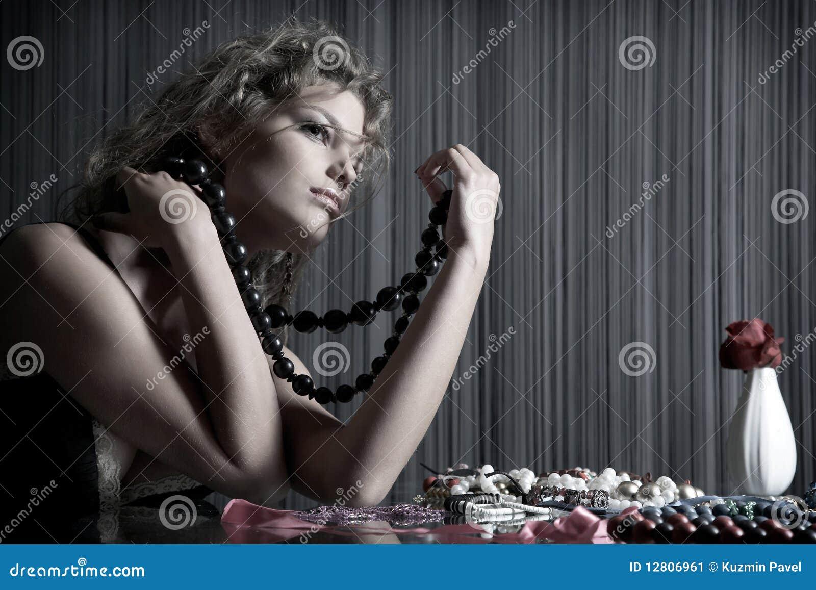 A menina da beleza senta-se na tabela com acessórios
