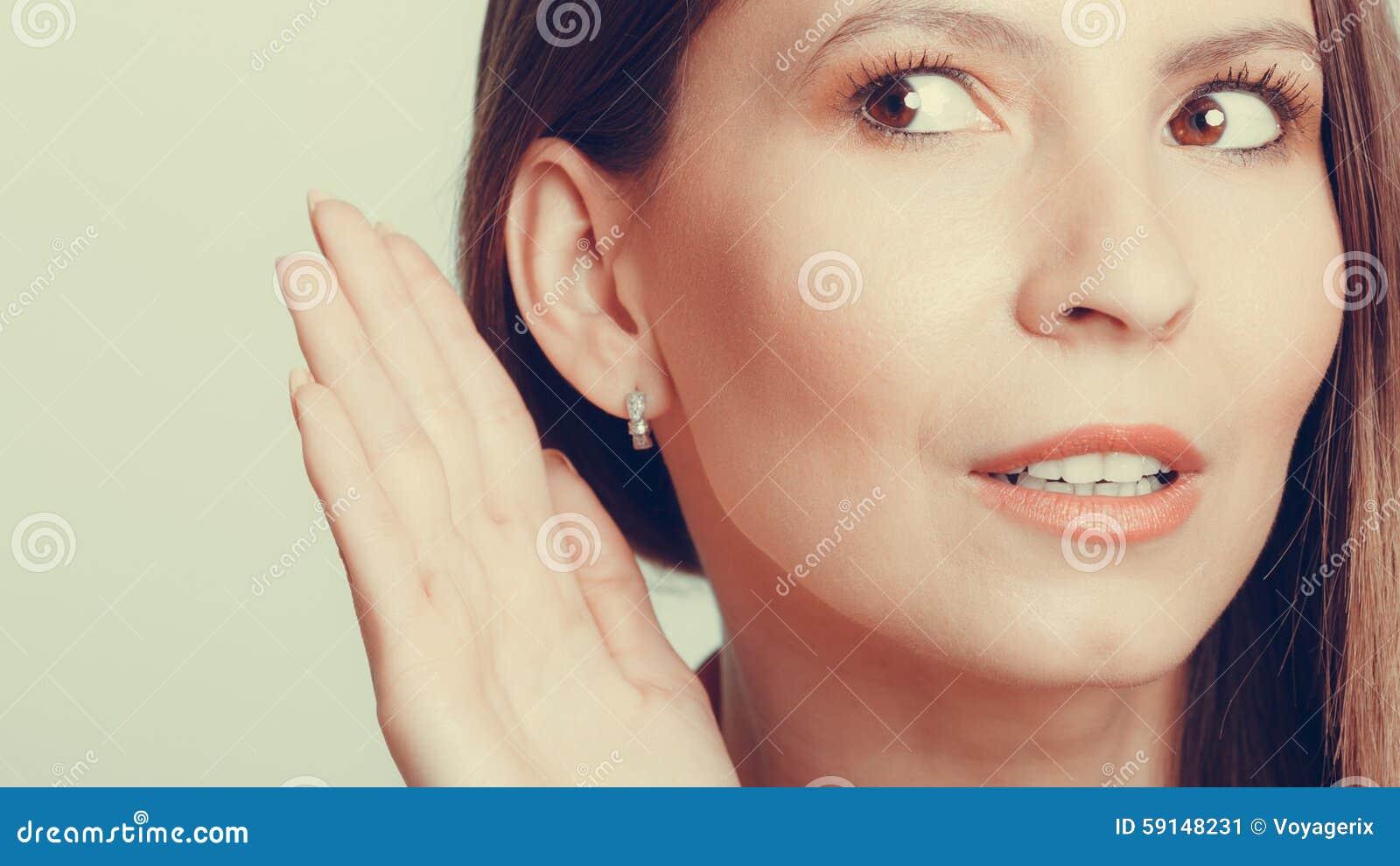 Menina da bisbolhetice que bisbilhota com mão à orelha