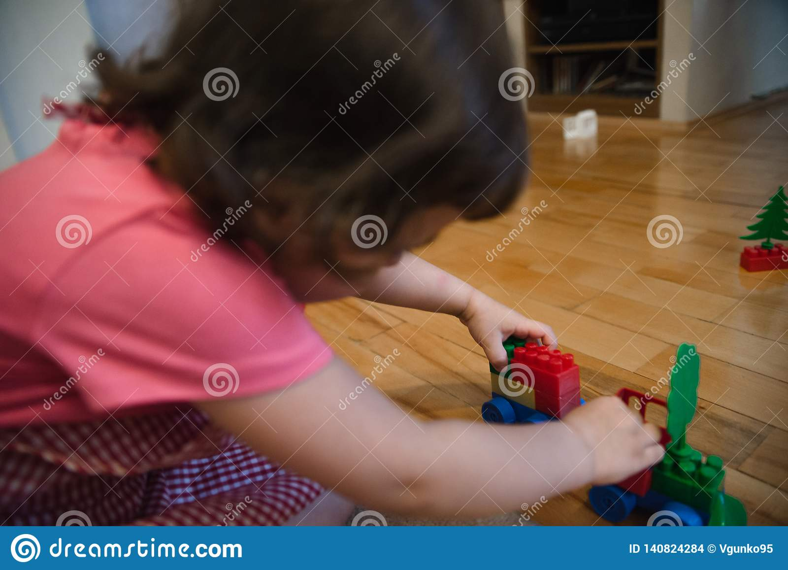 Menina da criança bonita que joga na casa