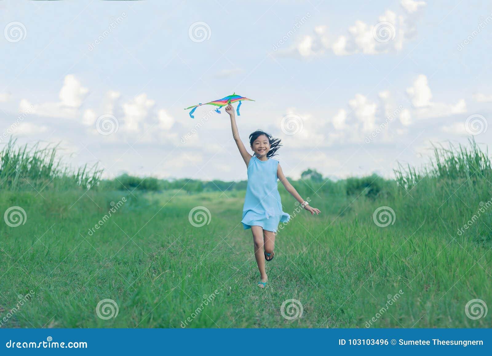 Menina da criança com um corredor do papagaio e feliz asiáticos no prado no summ