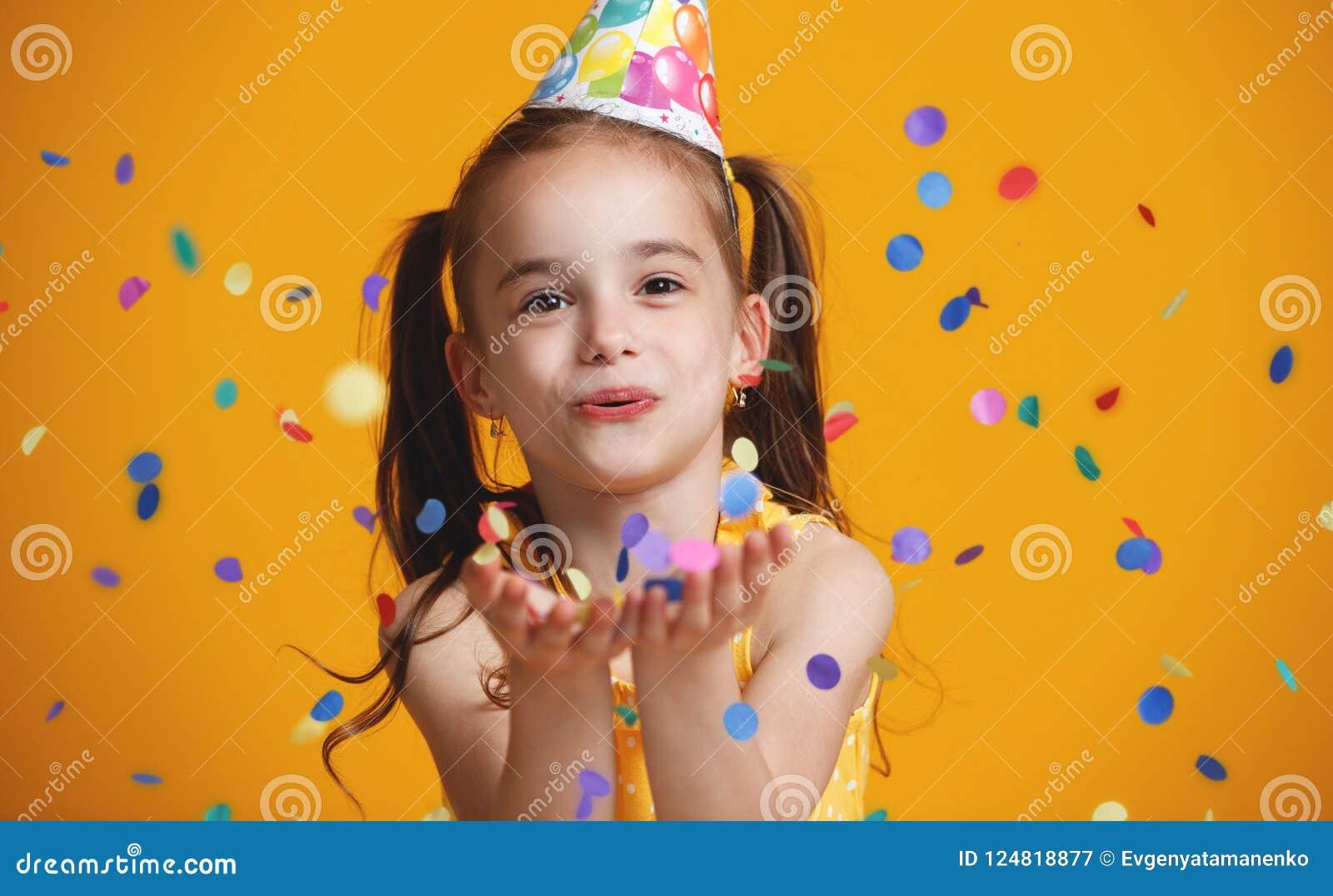 Menina da criança do feliz aniversario com confetes no fundo amarelo