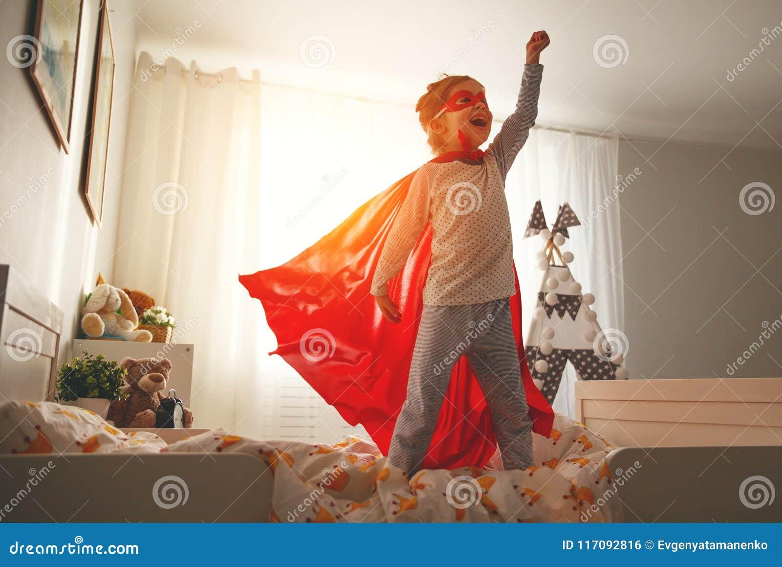 Menina da criança em um traje do super-herói com máscara e o casaco vermelho
