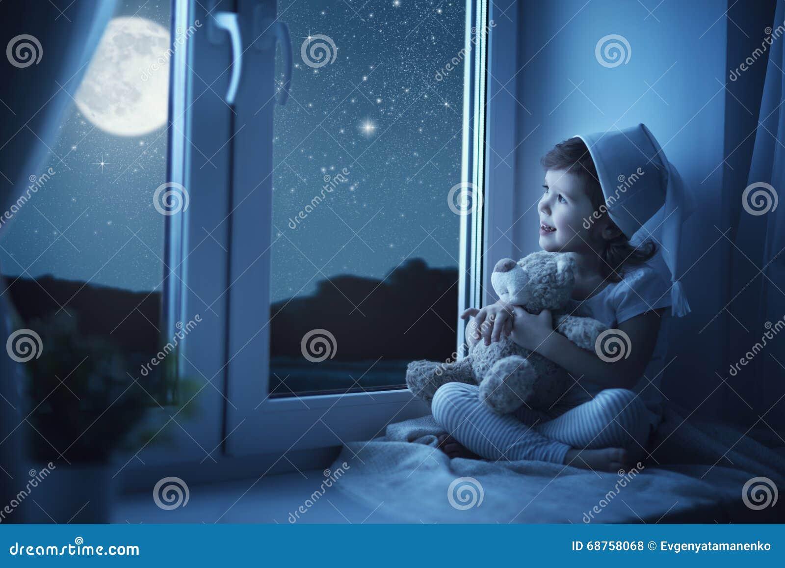 Menina da criança na janela que sonha e que admira o céu estrelado