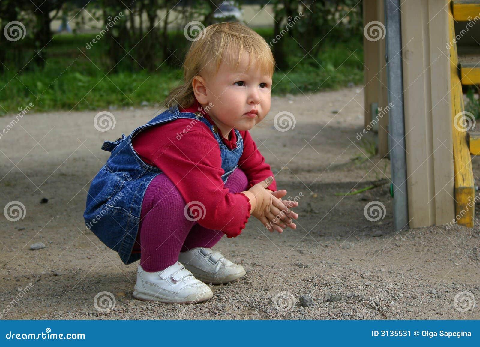 Menina da criança que joga com areia