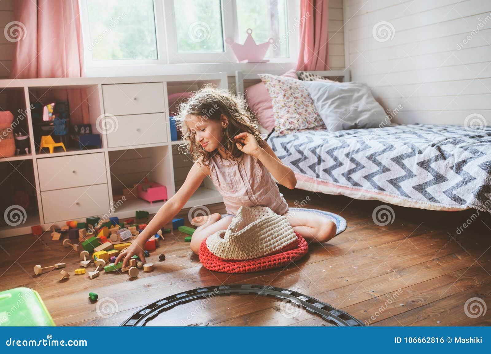 A menina da criança que limpa sua sala e organiza brinquedos de madeira no saco feito malha do armazenamento