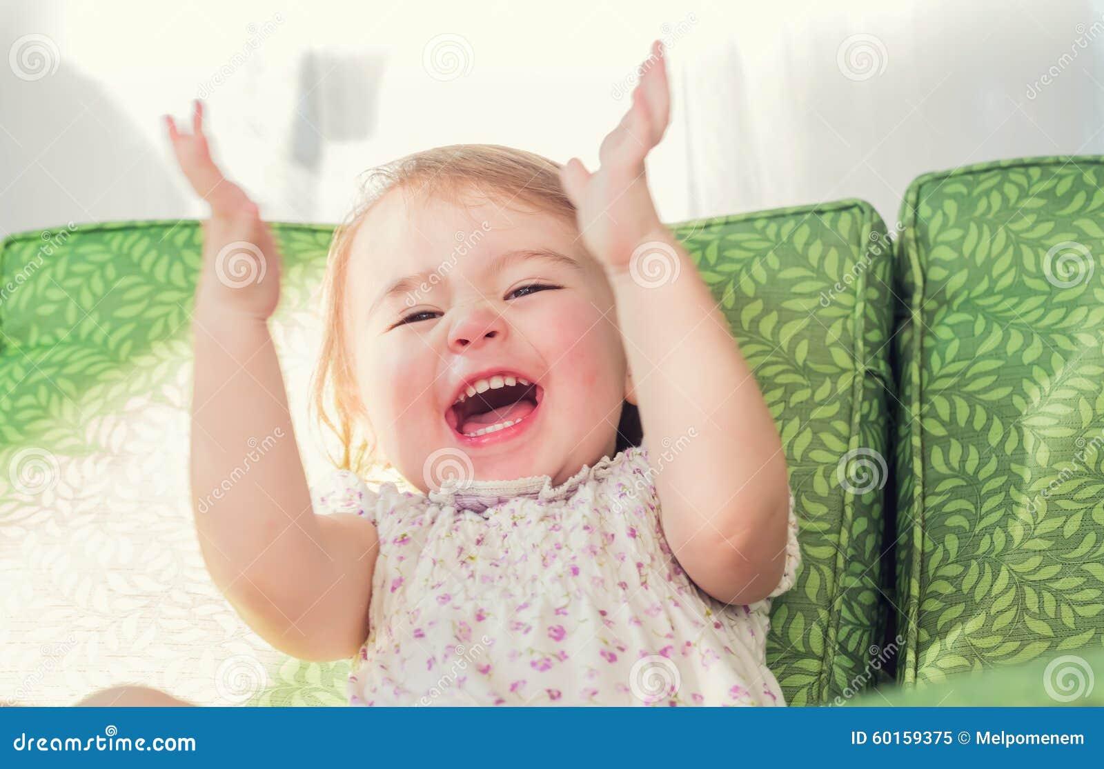 Menina da criança que sorri e que aplaude suas mãos