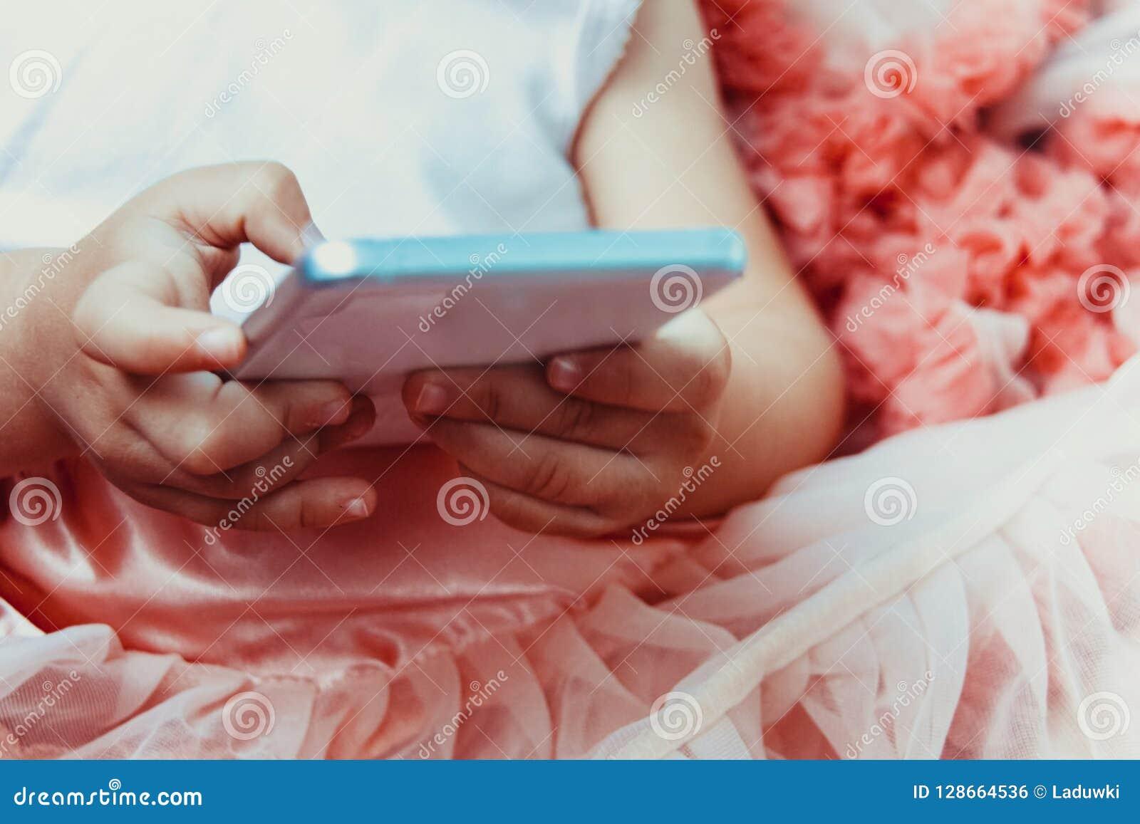 A menina da menina em uma saia cor-de-rosa macia bonita com plissados usa o telefone celular branco