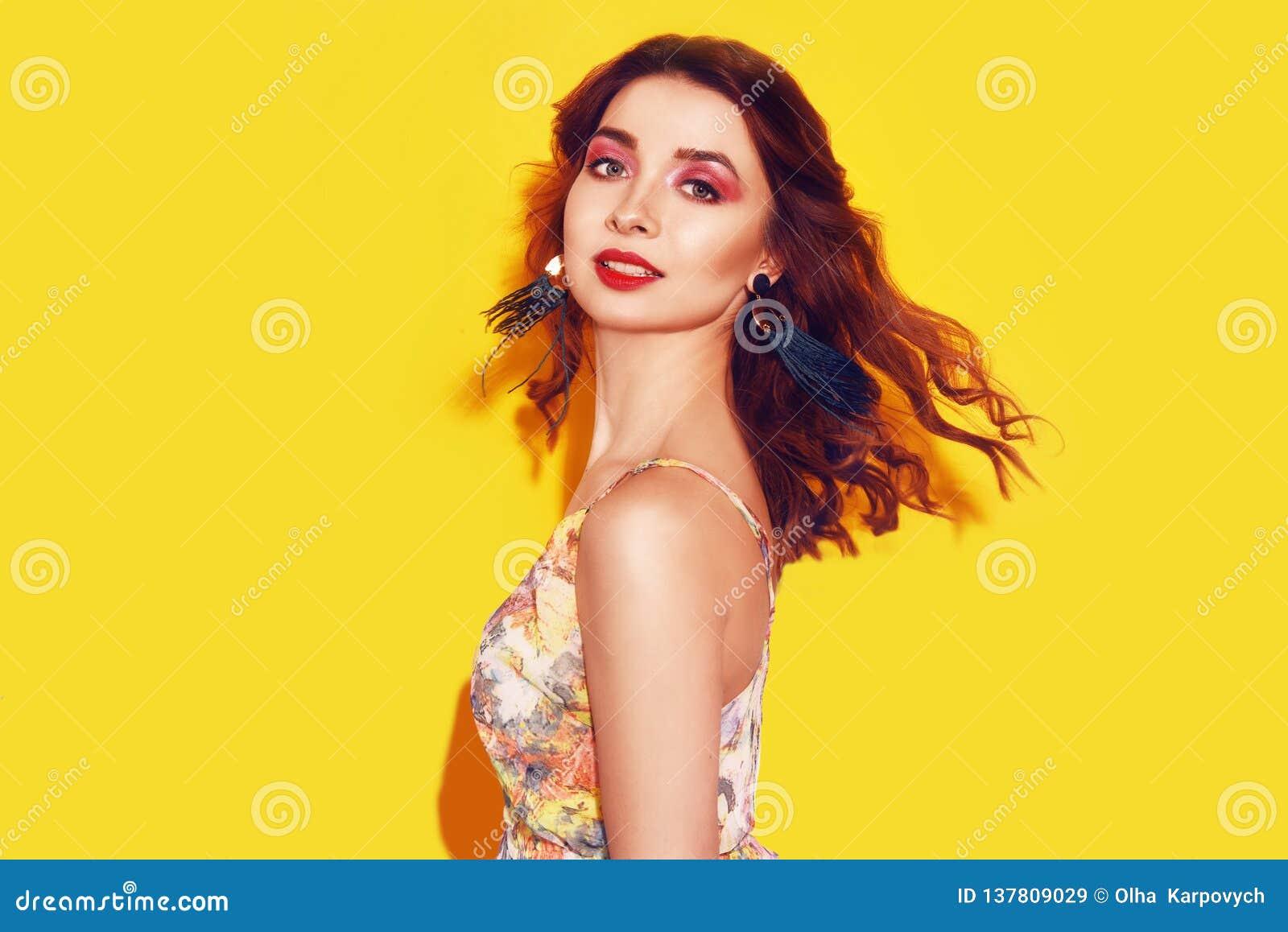Menina da forma no vestido na dança amarela do fundo A menina bonita com cabelo por muito tempo cerly de voo e o rosa compõem Men