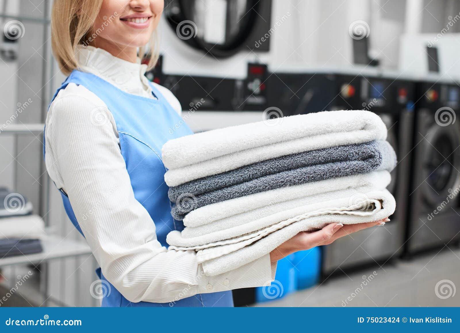 Menina da lavanderia do trabalhador que guarda toalhas frescas em seus mãos e sorrisos