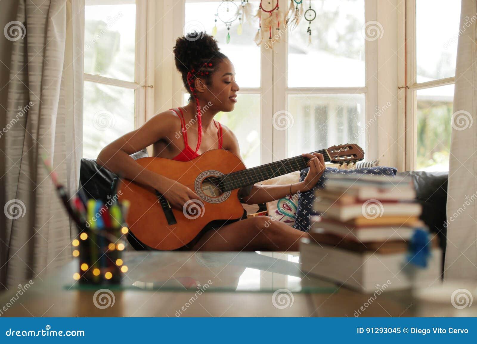 Menina da raça misturada que canta e que joga a guitarra clássica em casa