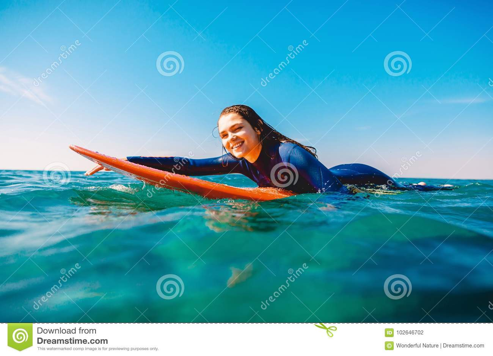 A menina da ressaca é de sorriso e de enfileiramento na prancha Mulher com a prancha no oceano Surfista e oceano