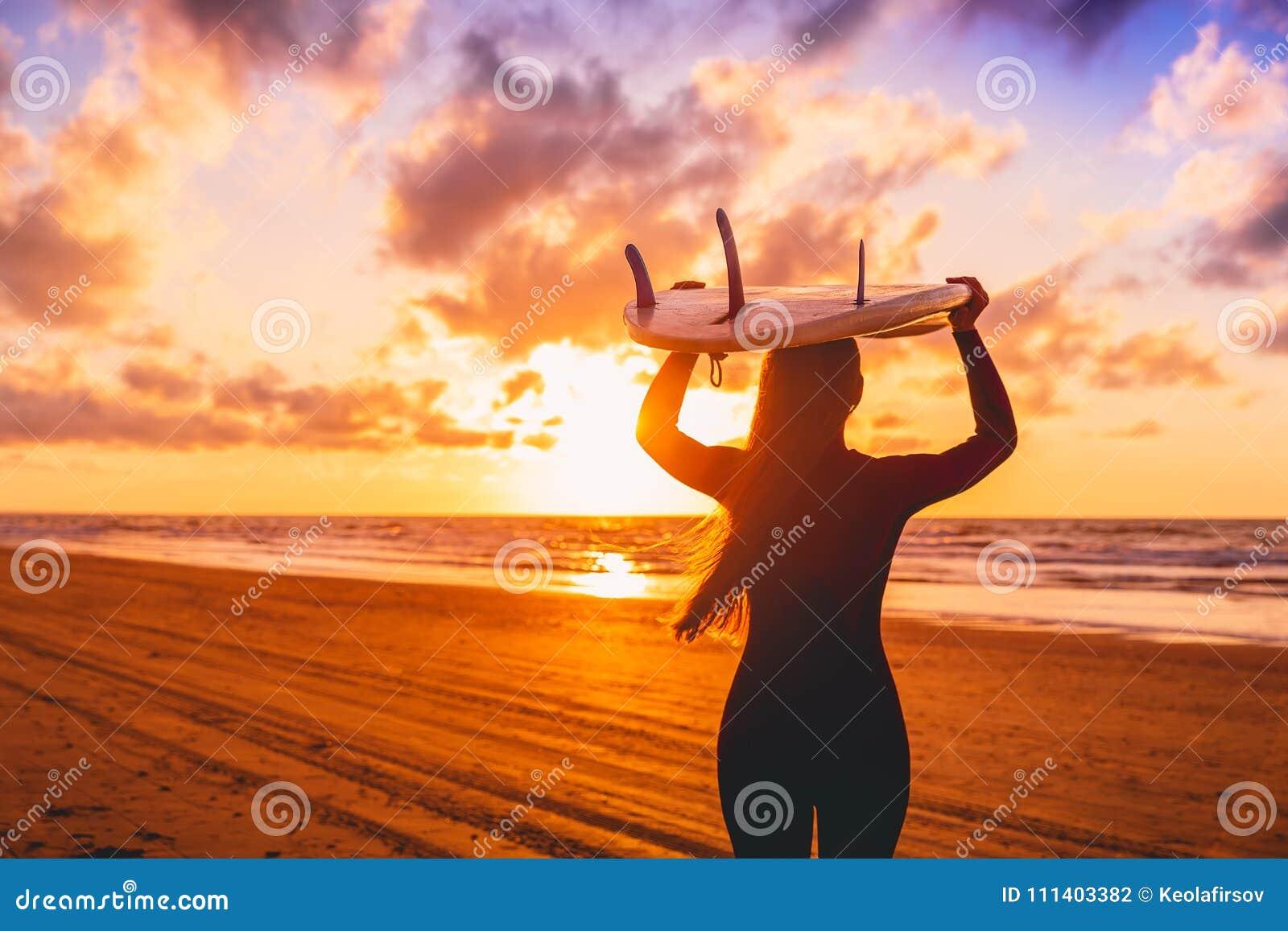 A menina da ressaca com cabelo longo vai a surfar Mulher com prancha em uma praia no por do sol