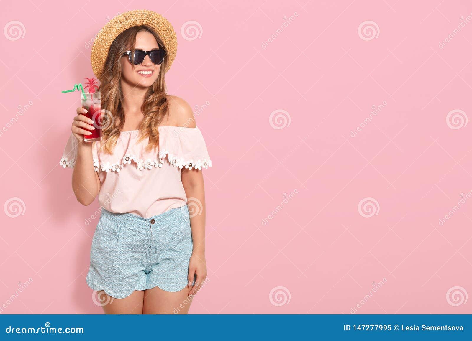 Menina de Bautiful nos óculos de sol, no chapéu de palha, na blusa do verão e no cocktail bebendo curto do verão, olhando o apart