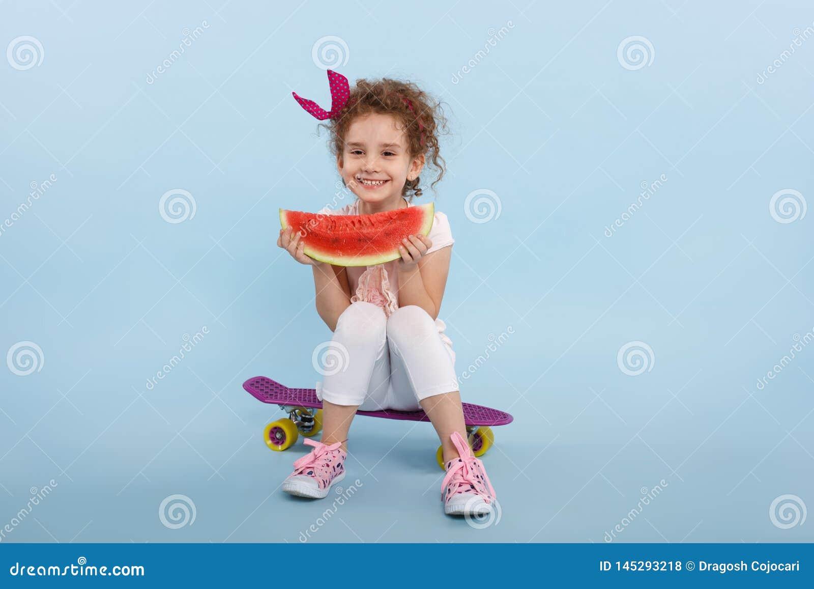 Menina de cabelo encaracolado pequena da felicidade com a melancia nas mãos, assentadas em um skate, isolado em um fundo azul