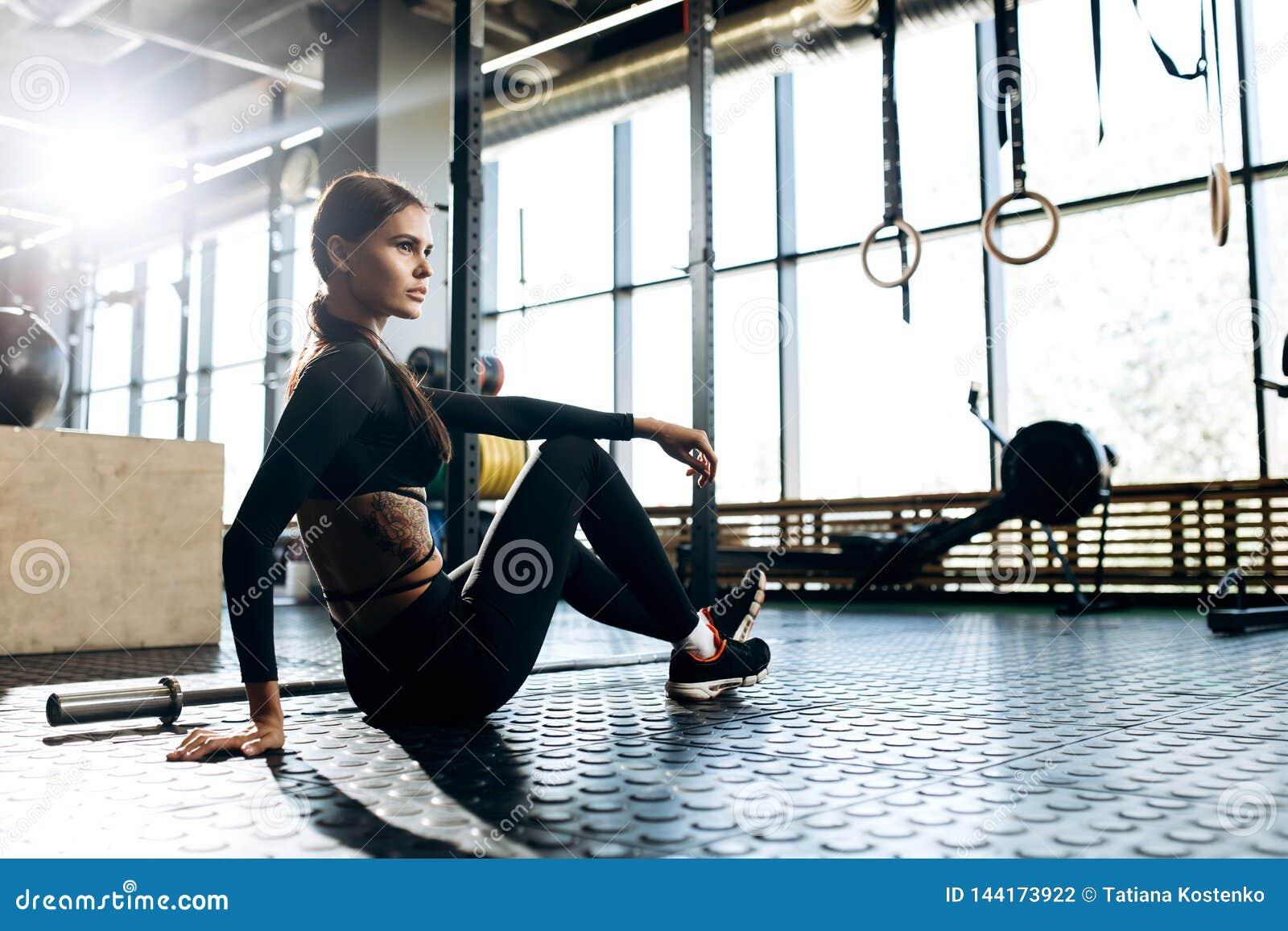 A menina de cabelo escuro magro vestida na roupa preta dos esportes está sentando-se no assoalho e está fazendo-se o esticão no g