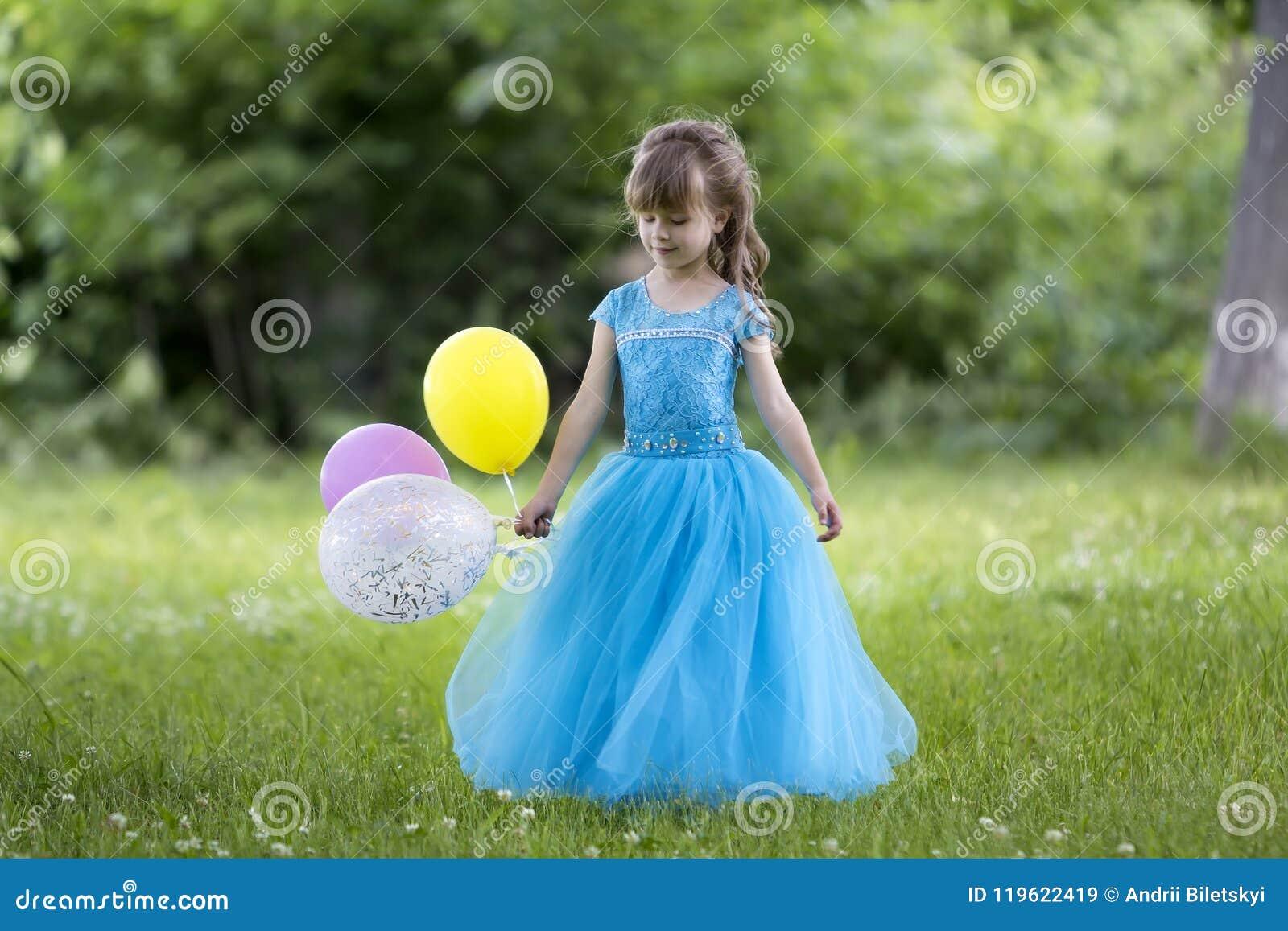 Menina de cabelos compridos loura consideravelmente pequena em d de nivelamento azul longo agradável