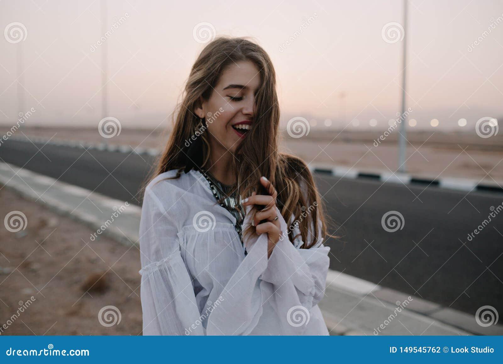 Menina de cabelos compridos de sorriso atrativa que levanta com os olhos fechados ao andar abaixo da estrada na noite do ver?o Re
