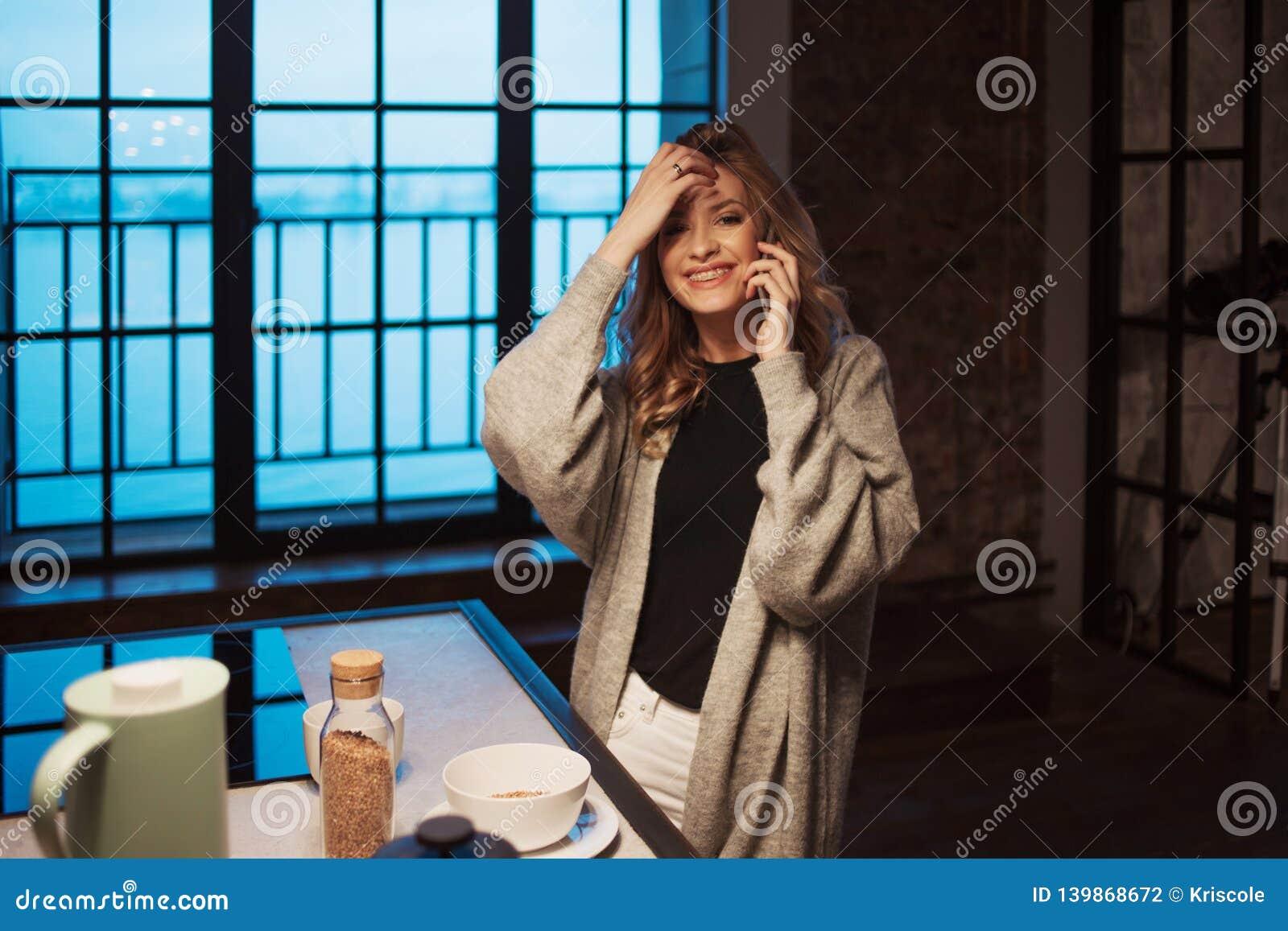Menina de encantamento na cozinha na manhã Fala no telefone e ter a jovem mulher do café da manhã A com a caneca em suas mãos