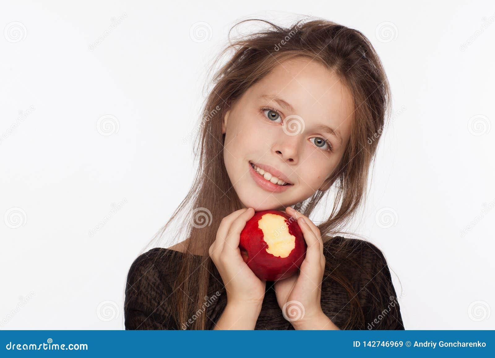 Menina de oito anos emocional bonita com uma maçã Sessão de foto no estúdio A menina está vestindo uma blusa preta