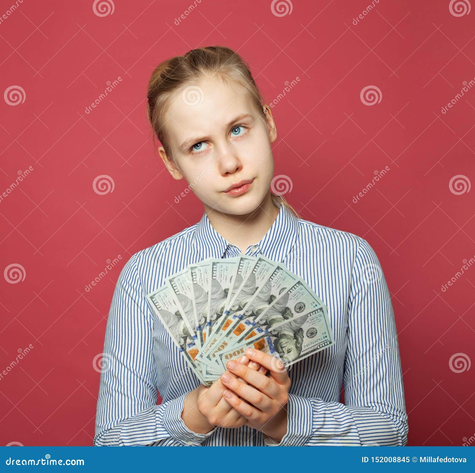 Menina de pensamento que guarda o dinheiro dólares americanos no fundo cor-de-rosa Orçamento do planeamento do adolescente